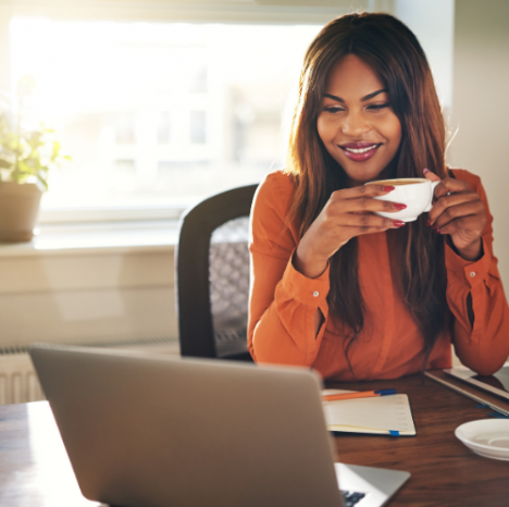 woman drinking coffee looking at a laptop